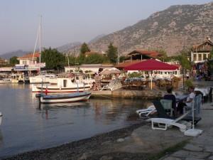 Selimiye: Holiday microcosm; a yacht, fishing boats, beach, sun loungers, restaurant, mini market and gift shop