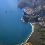Petrovac: Aerial view of the coast with the town, centre and Budva in the distance, top