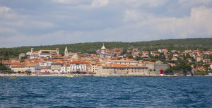 Krk Town: The beach, left, and breakwater with yacht masts behind, front the historic town