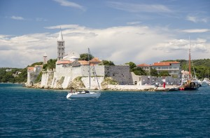 Rab Town: The harbour entrance with the white buildings contrasting against the woodland behind